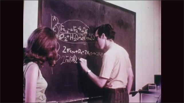 UNITED STATES 1970s: Two Students Writing Chemical Equations on a Blackboard