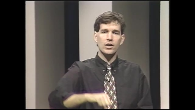 1990s: man on phone answering question asked by student audience