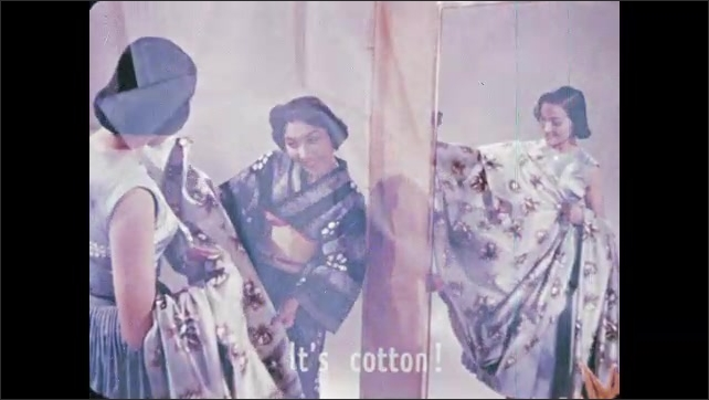 1950s: Fabric hangs from ceiling. Woman looks at dress in mirror while woman assists her. Subtitles appear. Woman holding fabric walks up to man at drawing of dress. They talk.