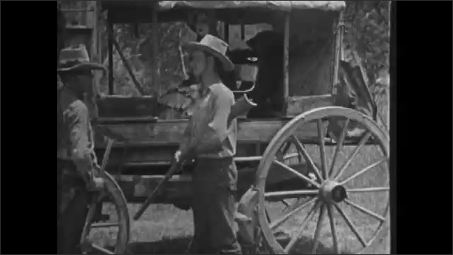 1920s: Cowboys assist woman into stagecoach. Indian hides in bushes. Indian rides horse out from behind bushes.