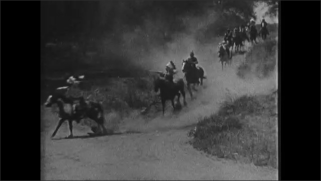 1920s: Indians ride horses down dirt road and fire guns.