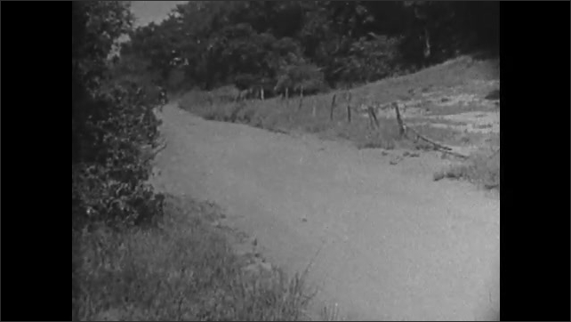1920s: Film of Indians chasing stagecoach runs in reverse. Indians pursue stagecoach down dirt road. Stagecoach and Indians exchange gunfire.