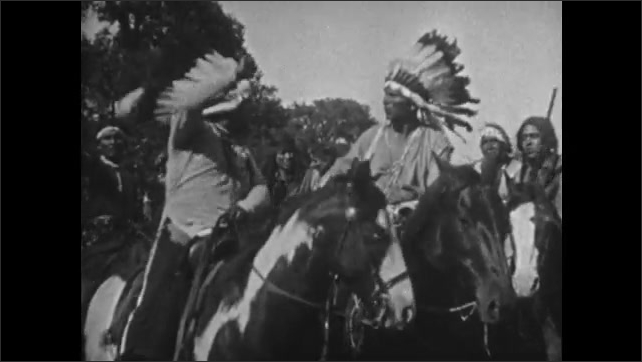 1920s: Indian chiefs talk and gesticulate on horseback. Indians ride from plains on horseback.
