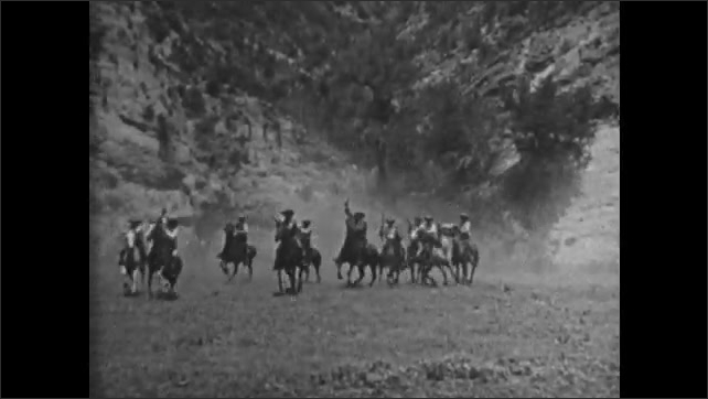 1920s: Cowboys chase Indians across plains on horseback. Cowboys and Indians exchange gunfire. Man on horseback rides toward overturned stagecoach. Cowboy dismounts and speaks to man and woman.