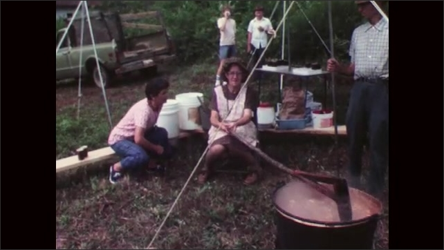1970s: Woman stands outside, holds wooden spoon and licks her finger, goes to bench where another woman sits who stirs a stew with a long stick, woman sits down, starts to talk to other woman.