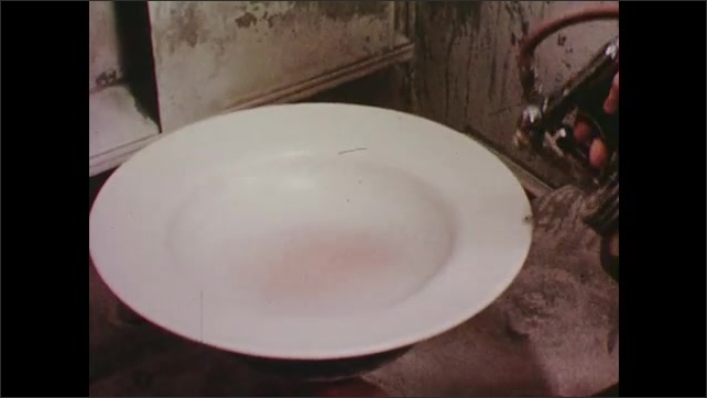 1940s: Hands spray glaze onto clay bowl with spray gun.