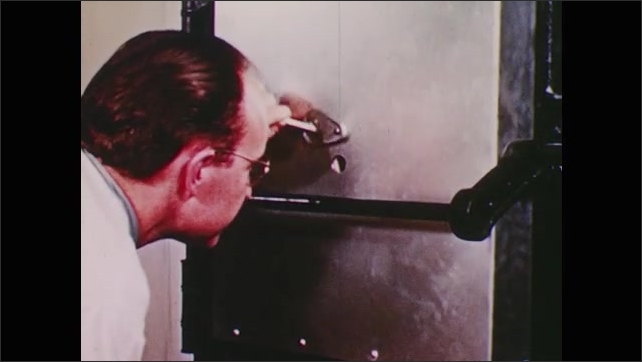 1950s: Man looks into peephole on kiln.  Bright red light.  Man flips switch.