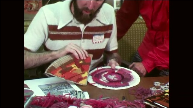 1970s: UNITED STATES: man holds shaped weaving. Needle weaving. Fan shaped weaving. Man sews in group.