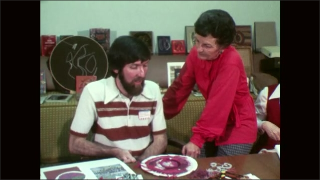 1970s: UNITED STATES: man weaves on shaped object. Man talks to lady in sewing class. Lady asks question
