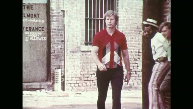UNITED STATES 1970s ?????As he enters an alley in the middle of the day, a man is surrounded by a gang.