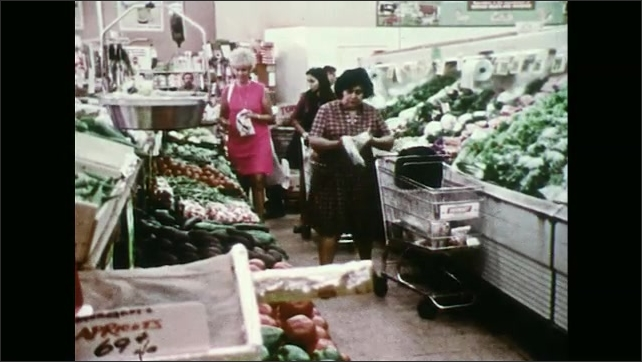 UNITED STATES 1970s ?????A woman shopping in a grocery leaves her bag in her cart and gets wallet stolen while weighing produce.