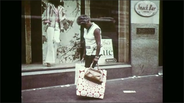 UNITED STATES 1970s ?????In a grocery a woman holds her bag while shopping as another lady keeps her bag close and a man places his wallet into his front pocket to prevent theft.