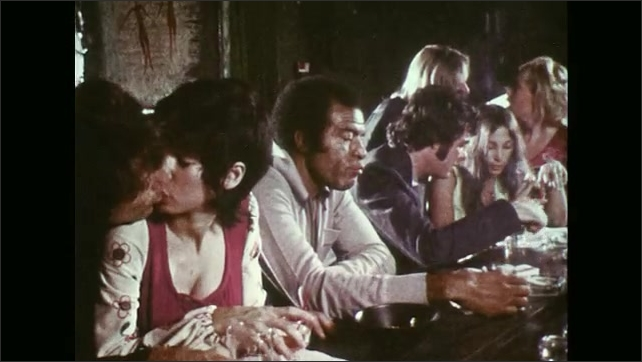 UNITED STATES 1970s ?????s people dance in a club, a man sits at a bar while a lady walks around dazed and confused.