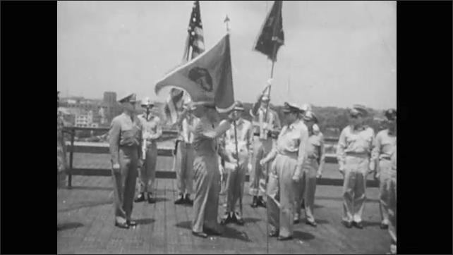 1950s: General MacArthur walks down steps from airplane. General MacArthur talks. Soldiers stand at attention holding flags.
