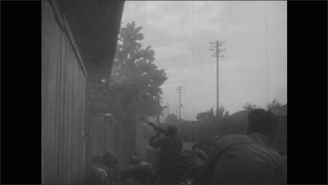 1950s: Soldiers hold on to guns. Soldier firing gun. Soldiers fire guns into building. Soldiers on vehicles driving down road.