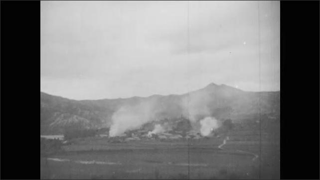 1950s: Battleships fire guns at sea. Guns on battleship fire. Artillery guns fire on ground. Smoke rises from distance. Wounded soldiers on stretchers.