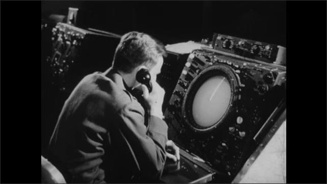 1940s: UNITED STATES: Senior Director scrambles interceptors. Man watches for blips on radar screen. Detection of intruders. Man speaks on telephone.