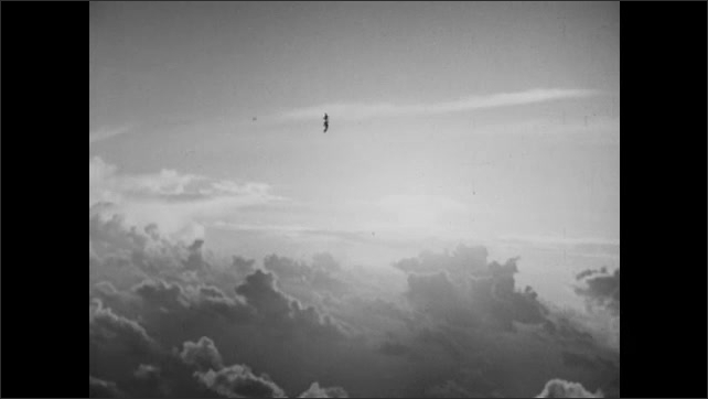1940s: UNITED STATES: view of ground from above. Clouds in sky. Missile strike. Sun shines through clouds.