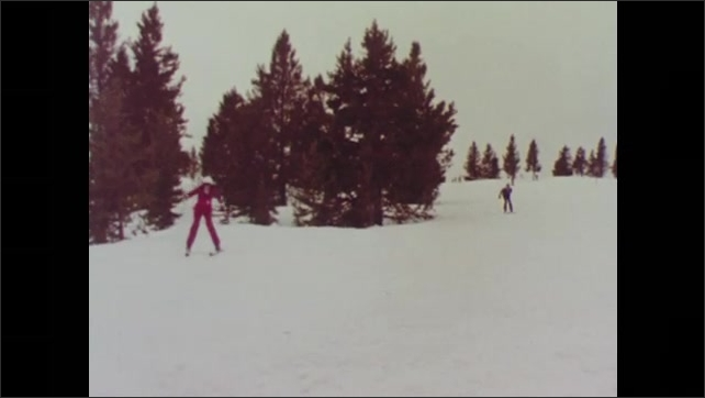 1970s: Man and woman ski down hill. Man and woman ski around pine trees. Man skis up to woman. Woman talks to man on snowy hill.