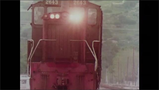 1970s: Car drives around gate at railway crossing. Train rolls down rail. Car backs around gate as train rolls through railway crossing. Train cars move past railway crossing gate.