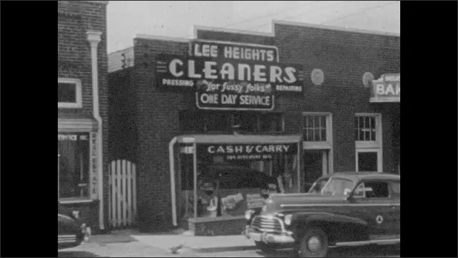 1940s: Storefronts and facades, sign ??obertson???? woman stands on the sidewalk, cars parked. Buildings under construction, man rides bicycle. Suburban houses under construction.