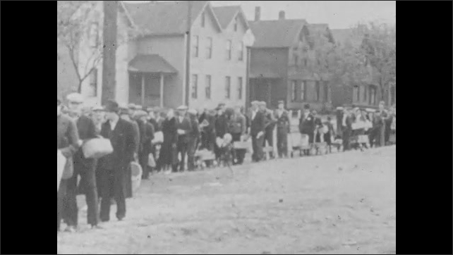 1940s: Man looks through garbage bin. People stand in line with baskets. Hands warm by fire bin. People move in line. Old man speaks, people stand behind. Face of man with hat. Demonstration.