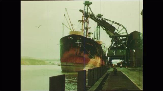 1950s: large cargo ship passing sailboat and another cargo ship, pulley system moves sugar and pulp onto conveyer belt