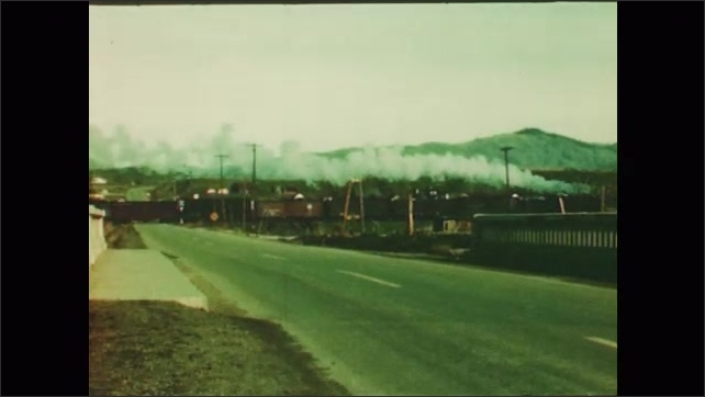 1950s: field dotted by homes and buildings, train driving past bridge, small town