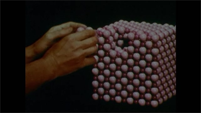 1950s: Hand grabs cluster of marbles from model of sodium chloride. Hand puts cluster of marbles back into cube.