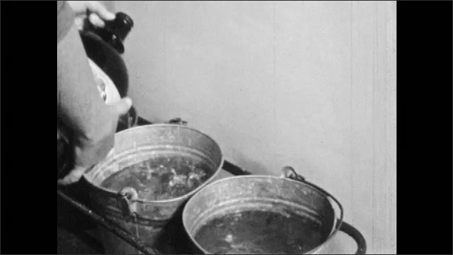 1960s: Person sprays water through nozzle into buckets. Person pours liquid bacteria into buckets of water then removes the buckets.