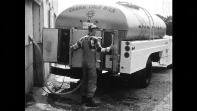 1960s: Man takes hose from milk truck and puts it through hole in door to dairy. Man grabs tool from milk truck and walks away.
