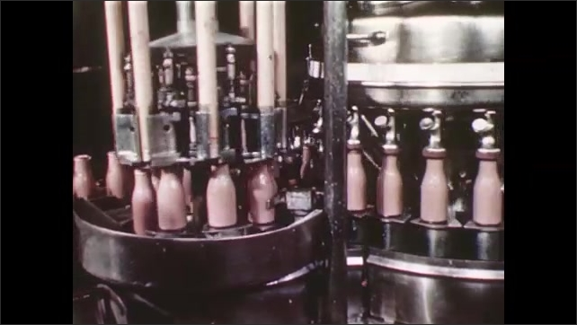 UNITED STATES 1940s: Bottles being loaded onto rotating conveyer belt and filled with chocolate milk