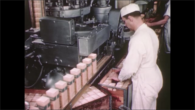 UNITED STATES 1940s: Factory worker inspecting and removing cartons of milk from conveyer belt and placing them into a crate.