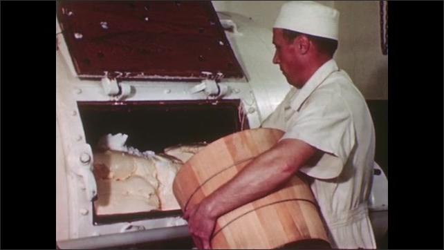 UNITED STATES 1940s: Dairy worker scooping salt from a wooden barrel into a large churn filled with butter.