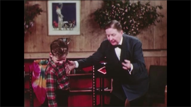 UNITED STATES 1940s: A man in a bow tie pulls a chicken out of a hat as a boy laughs.