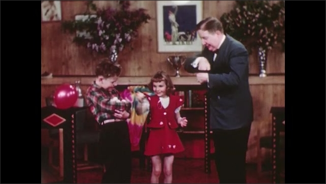 UNITED STATES 1940s: A man pulls a series of eggs out of a hat, hands the eggs to a little girl, who then places the eggs in the cupped arms of a boy.