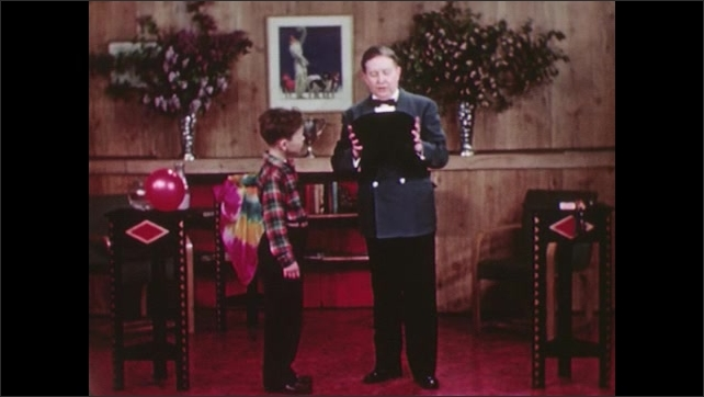 UNITED STATES 1940s: A man holds a top hat out to a boy, the boy looks inside the hat, shakes his head, the man makes a sweeping gesture in the air.