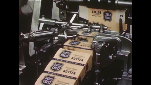 UNITED STATES 1940s: Blocks of butter being packaged by machine, then factory workers load the packaged blocks into carboard boxes.