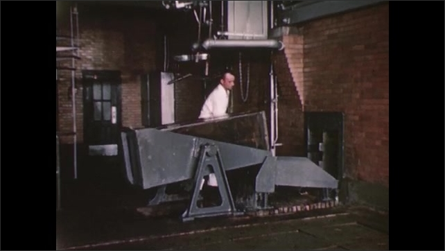 UNITED STATES 1940s: A man empties a large block of ice from a metal container onto a chute.