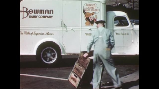 UNITED STATES 1940s: A milkman removes crates of dairy products from a parked milk delivery truck and stacks them onto a hand cart.