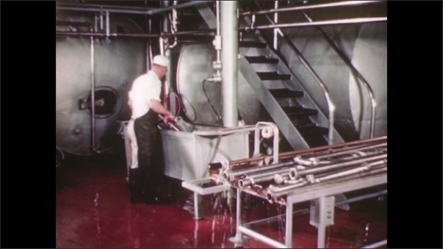 UNITED STATES 1940s: A factory worker removes a pipe from a large machine with a wrench and places it into a steel basin, then  removes the pipe from the basin and slides in over a smaller pipe.