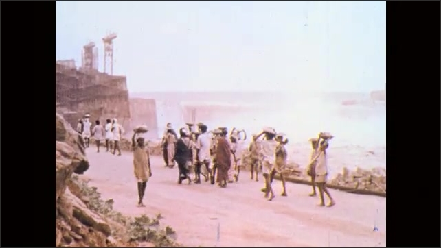 1970s, India: Women walk, carrying supplies on their heads. People walk down path to dam. People walk down hill path, carrying supplies.