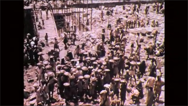 1970s, India: Crowds of people work on top of dam and scaffolding platforms, carrying supplies. Overhead view of people carrying rocks on head, tossing them.