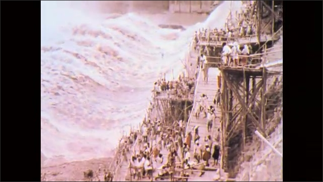 1970s, India: Throngs of people move in rows, carrying poles and rocks. People work on scaffolding beside rushing water. People carry supplies on scaffolding outcrop at rushing dam.