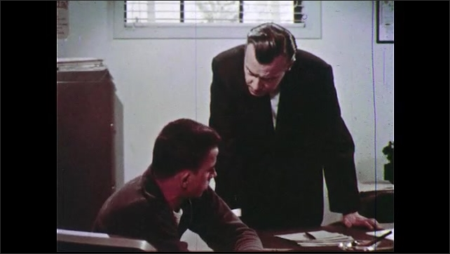 1960s: UNITED STATES: boy talks to physician in office. Boy sits in doctor's room.