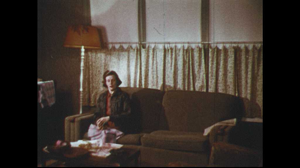 1960s: UNITED STATES: girl arrives home. Girl takes off coat. Lady sits on sofa. Girl talks to lady