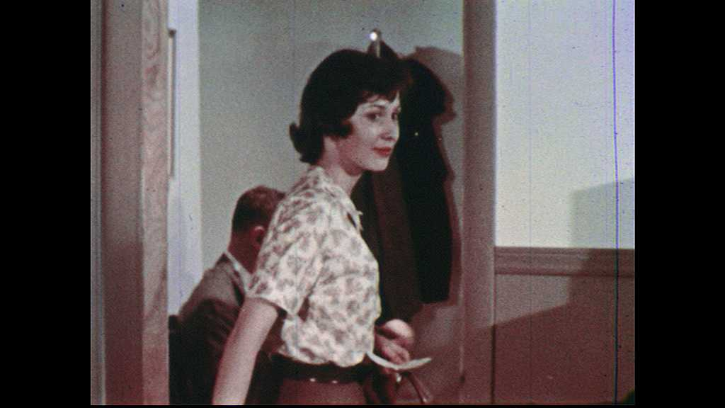 1960s: UNITED STATES: lady leaves office. Lady nods head. Doctor sits at desk looking worried. Close up of doctor's face.