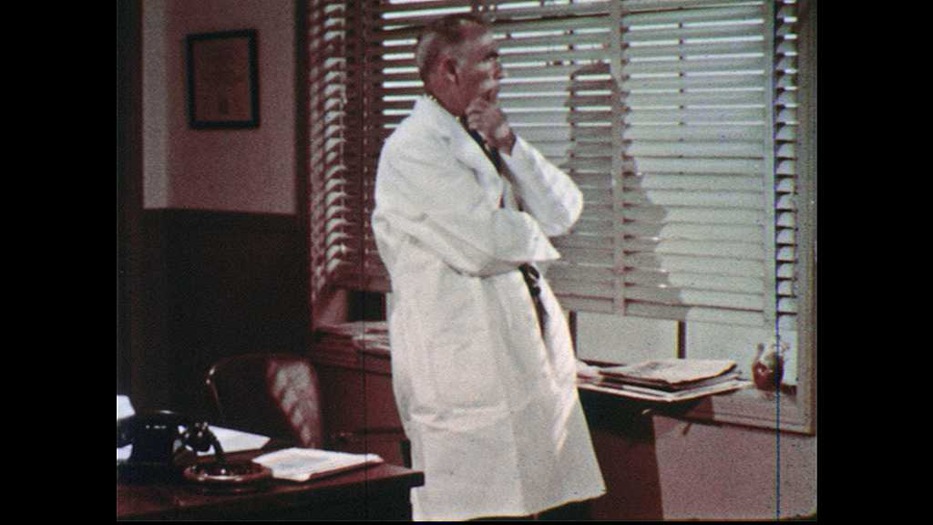 1960s: UNITED STATES: doctor thinks to self. Doctor opens desk rawer. Doctor finds number. Doctor picks up telephone
