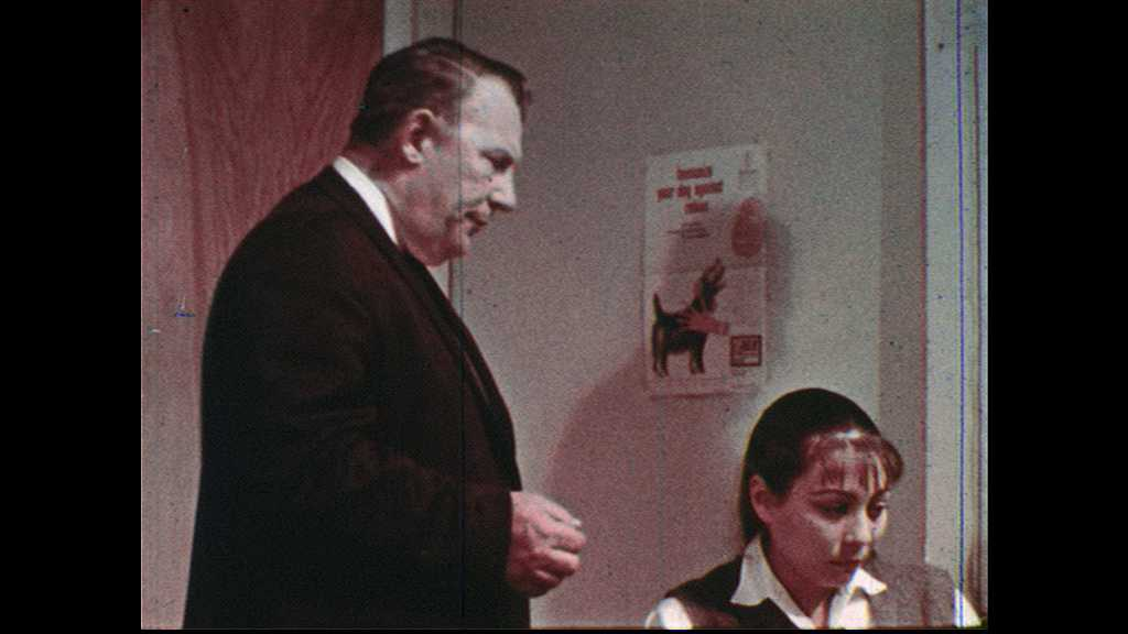 1960s: UNITED STATES: physician talks with man and lady in office. Girl sits at desk