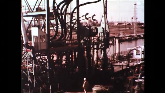 UNITED STATES 1970s: Men Transferring Shipment of Sour Crude Oil Products from Tanker to Refinery